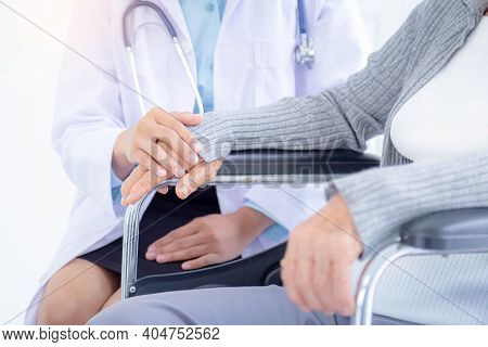 A Female Doctor Holing Senior Patient's Hands And Comforting Her. Disabled Elderly And Senior Homeca