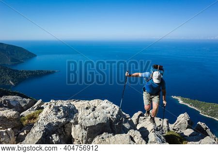 Hiking on Lycian way. Man with backpack balancing on rock cliff high above Mediterranean sea on Lycian Way trail, Trekking in Turkey, Amazing coastline blue water