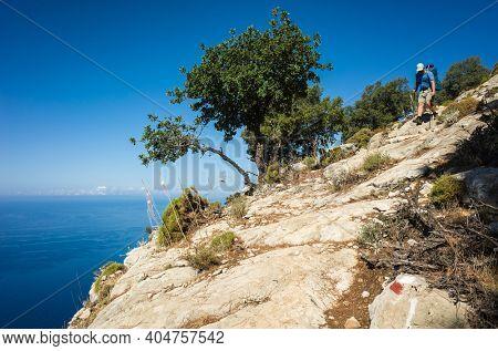 Hiking on Lycian way. Man with backpack walking down on steep rock slope high above Mediterranean sea on Lycian Way trail, Trekking in Turkey