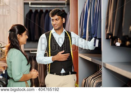 Shop Assistant Showing Young Woman Assortment Of Jackets And Male Suit In Store