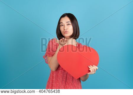 A Romantic, Lovesick Young Asian Woman In A Red Dress Holds A Large Red Paper Heart And Blows A Kiss