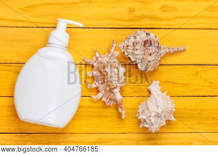 Bottle Of Suntan Cream With Shells On A Yellow Wooden Background. Beach Vacation. Top View