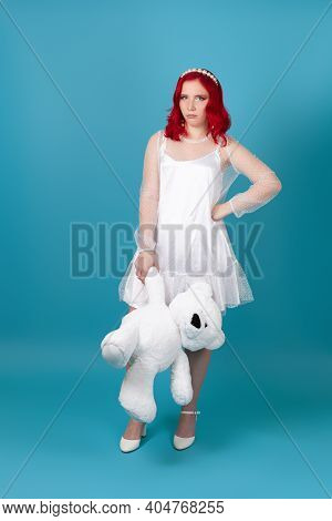 Full-length Disappointed, Sad, Resentful Young Woman In White Dress With Red Hair Holding A White Te