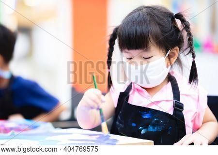 Students Girl Were Concentrating On Painting With Brushes And Watercolor On The Canvas. Little Asian