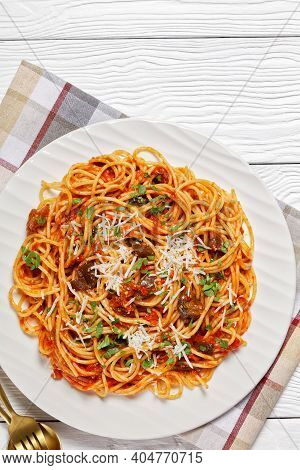 Pasta Spaghetti Alla Norma On A White Plate On A White Textured Wooden Table With Golden Spoon And F