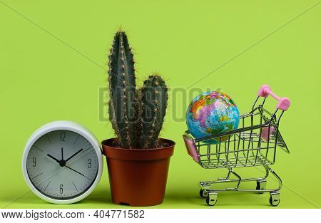 Global Supermarket, Shopping Time. Cactus In Pot, Clock And Supermarket Trolley With Globe On Green