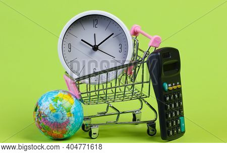 School Supplies With A Sopping Trolley On Green Background. Shopping Cart, Globe, Calculator, Clock.