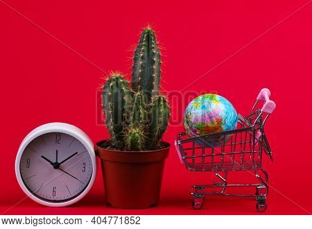 Cactus With Shopping Cart, Globe, Clock On Red  Background. Shopping Time