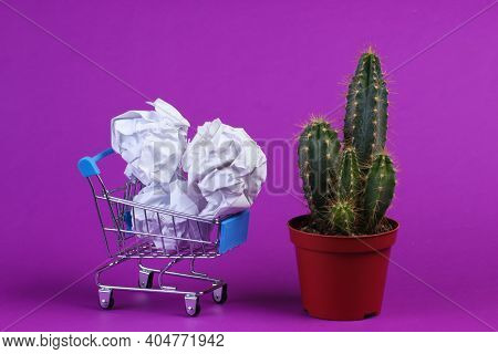 Cactus In Pot And Shopping Trolley With Crumpled Paper Balls On Purple Studio Background. Minimalism