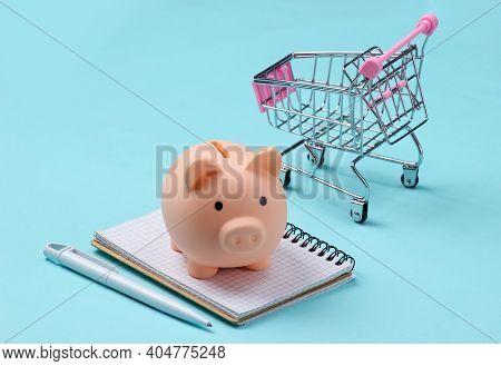 Piggy Bank And Notebook, Supermarket Trolley On Blue  Background. Shopping List, Budget. Minimalisti