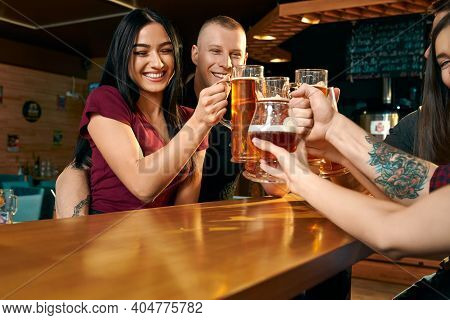 View From Side Of Happy Woman And Man Hugging Each Other And Toasting With Friends In Pub. Company D