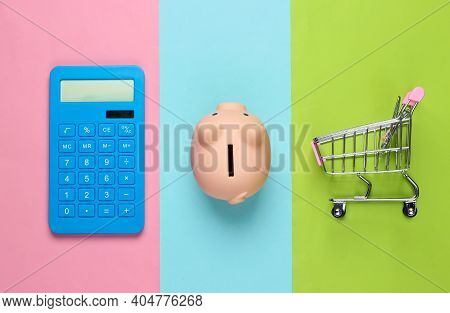 Piggy Bank And Calculator, Shopping Trolley On Colored Pastel Background. Minimalistic Studio Shot.