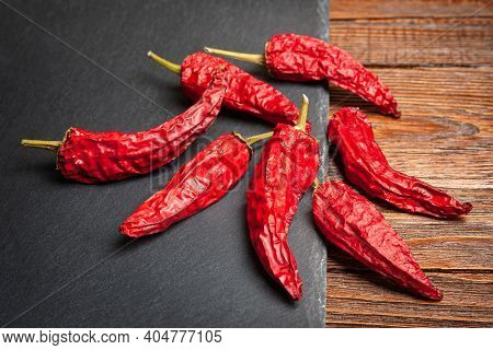 Red Pepper. A Pile Of Dry Red Peppers Stacked On A Black Slate Stone. Hot Chili Peppers. Spices For