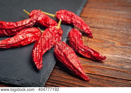 Red Pepper On The Table. A Pile Of Dried Red Peppers Stacked On A Black Slate Stone. Hot Chili Peppe