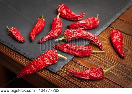 Red Pepper. A Pile Of Dry Red Pepper Lying On The Wooden Table. Hot Chili Peppers. Spices For Cookin