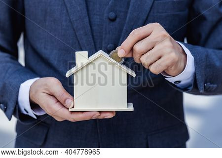 Businessman Hand Putting Coin In Model House Piggy Bank Saving Money Financial For Buy Home. Save An