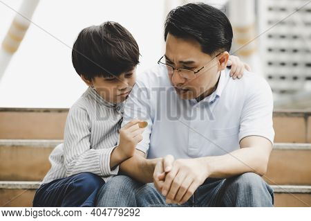 Poor Child Look At Coin And Get Sad While Father Embracing And Console His Son During They Sitting I