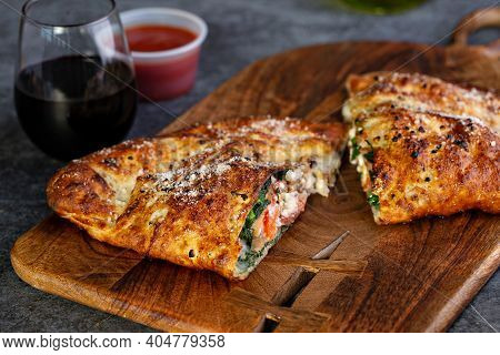 Traditional Calzone Cut In Half Served With Marinara Sauce