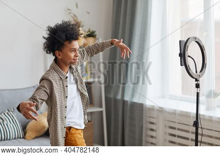 Side View Portrait Of Teenage African-american Boy Filming Videos At Home And Dancing To Camera Set