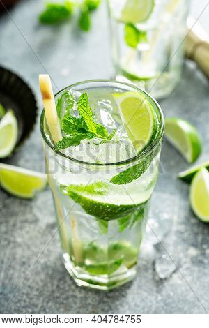 Refreshing Mojito Cocktail With Lime And Mint In A Tall Glass With A Sugar Cane Stick