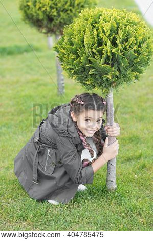 Play Hide And Seek. Girl Cute Kid Green Grass Background. Healthy Emotional Happy Kid Relaxing Outdo