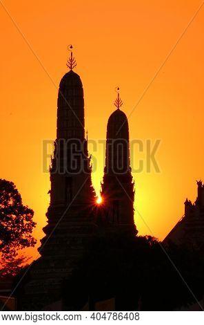Setting Sun Shining Through The Silhouette Of Wat Arun Temple Spires, Bangkok, Historicplace In Thai