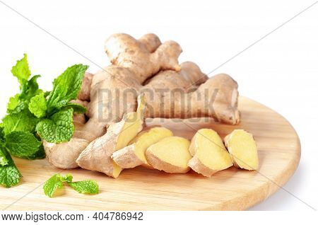 Fresh Sliced Ginger Root And Green Mint Leaves On A Round Cutting Board. Ingredients For Ginger Herb