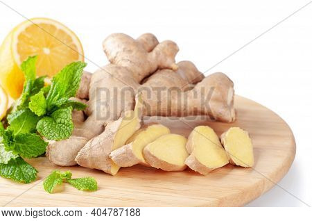 Fresh Sliced Ginger Root, Lemon And Green Mint Leaves On A Round Cutting Board. Ingredients For Ging