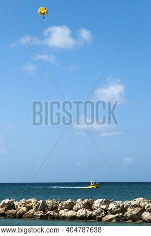 The Motorboat Pulling The Parachute With A Couple Of Tourists High In The Air Along Grand Cayman Isl
