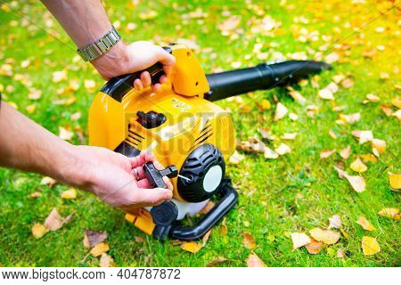 Starting A Handheld, Cordless Leaf Blower In A Garden To Cleaning A Lawn.