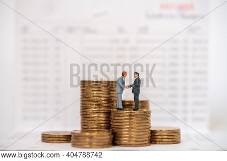 Business Money Saving And Work Concept. Two Businessman Miniature Figure People Stabding And Make Ha
