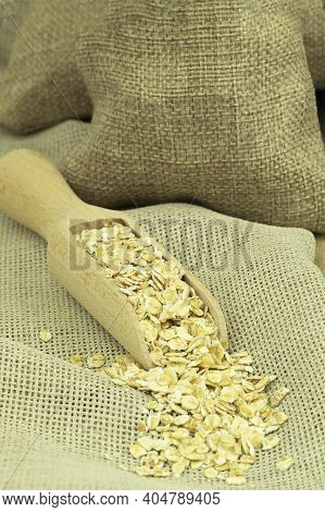 Oatmeal In A Bag On A Wooden Background With Space For Text. Oatmeal On Burlap With A Wooden Spoon.