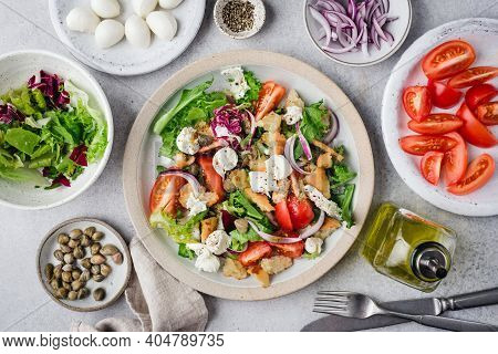Healthy Salad With Tomatoes, Croutons, Greens And Mozzarella Cheese On A Plate. Italian Style Panzan