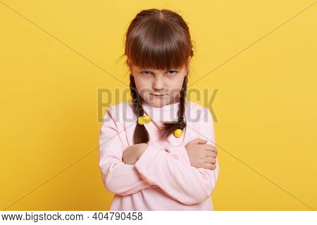 Adorable Beautiful Little Offended Girl Isolated Over Yellow Background, Dresses Casually, Looks Fro