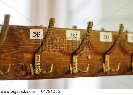 Wardrobe, Clothes Hooks Are Numbered. Coat Rack With Hooks For Coats And Jackets In A Museum. An Emp