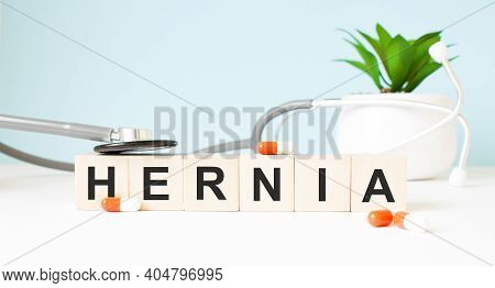 The Word Hernia Is Written On Wooden Cubes Near A Stethoscope On A Wooden Background. Medical Concep