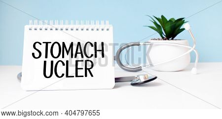 The Text Stomach Ucler Is Written On Notepad Near A Stethoscope On A Blue Background. Medical Concep
