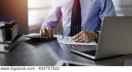 Unknown Male Accountant Use Calculator And Computer With Holding Pen On While Staying At Home During