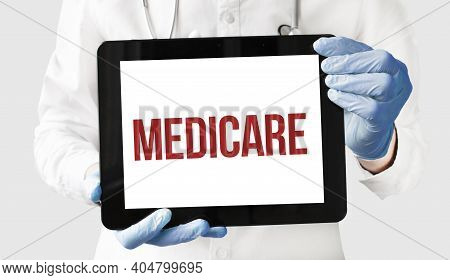 Doctor In Holds A Tablet With Text Medicare