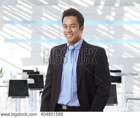 Portrait of happy asian businessman at office lobby, smiling.
