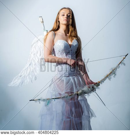 Pretty White Little Girl As The Cupid With A Bow And Arrow Congratulating On St Valentines Day. Vale
