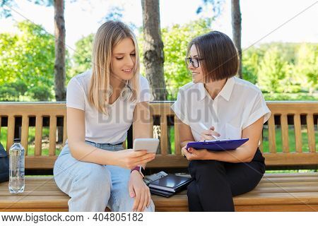 Woman Psychologist, Social Worker, Teacher Talking With University Student Sitting On Bench In Colle