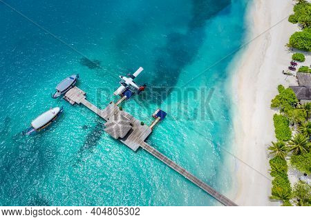 Aerial View Of A Tropical Island In Turquoise Water And Jetty Pier Top View. Luxurious Over Water Vi