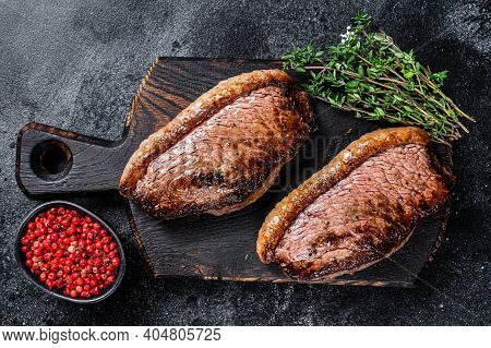 Bbq Grilled Top Sirloin Cap Or Picanha Steak On A Wooden Cutting Board. Black Background. Top View