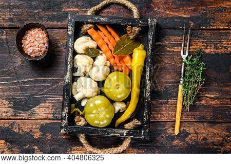 Homemade Marinated And Pickles Vegetables Preserve On A Wooden Tray. Dark Wooden Background. Top Vie