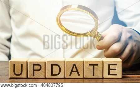 Wooden Blocks With The Word Update And A Magnifying Glass. Updating The Version Or Software Componen