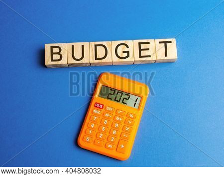 Wooden Blocks With The Word Budget And Calculator 2021. Accumulating Money And Planning A Budget. Bu
