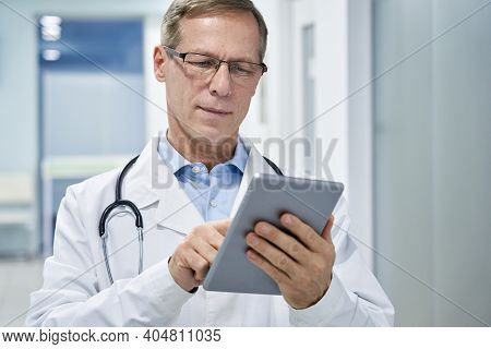 Old Senior Male Doctor Holding Digital Tablet In Hands Using E Health Technology Apps In Hospital Co