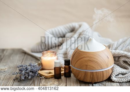Modern Aroma Oil Diffuser On Wood Surface With Knitted Element, Candle And Lavender Oil On A Blurred