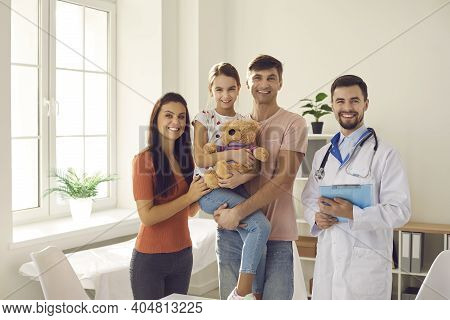 Portrait Of Smiling Young Mum, Dad And Their Child Together With Their Family Doctor